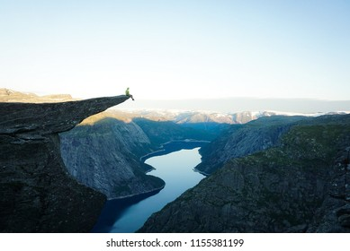 Man on Trolltunga cliff edge happy quince yoga. Traveling in Norway adventure lifestyle extreme vacations outdoor sunrise mountains landscape aerial view