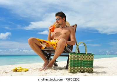 Man on a tropical beach with cocktail