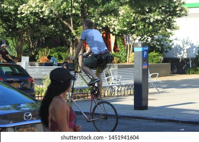 a man on a very high bicycle zooming thru traffic on Fulton street in the crown heights section on a very hot summer day in Brooklyn NY July 15 2019