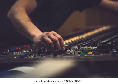 Man on the vintage sound console moving knobs and mixing music.