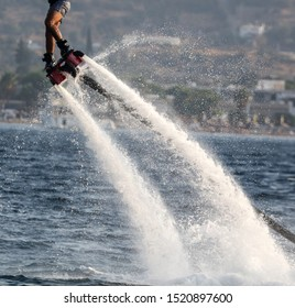 A man on a water attraction at sea. Flyboard