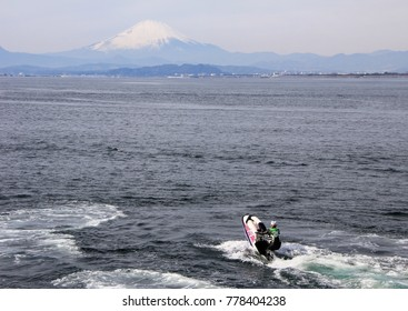 Man on the water bike in Pacific ocean and Mount Fuji on background. Nature of Japan. Kamakura, Japan, 06.01.2013.