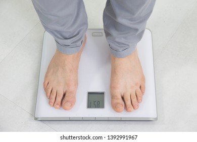 A man on weight scale.