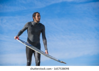 Man on a wetsuit standing on the beach while preparing to run while holding his skimboard