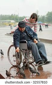 Man on a wheelchair feeding birds.