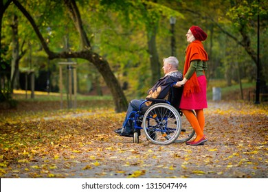 man on wheelchair with happy young woman in the park in autumn