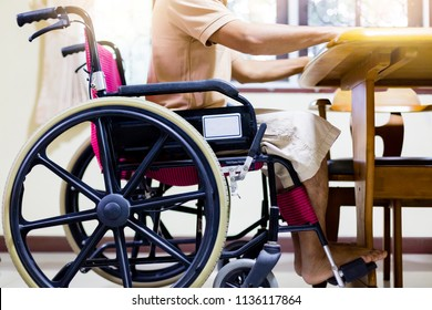 Man on wheelchair. He ready to have food on wooden table in home.