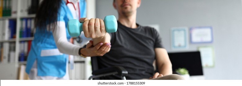 Man on wheelchair holds dumbbell in his hands. Doctor and young man in wheelchair. Treatment and restoration lost functions. Rehabilitation after injuries. Restoration motor functions hand