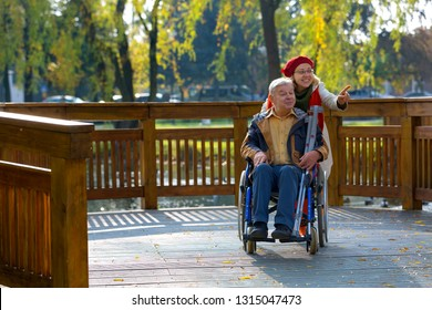 man on wheelchair with optimistic young woman in the park with trees in the background