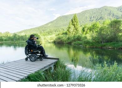 man on wheelchair using mirrorless camera near the lake in nature