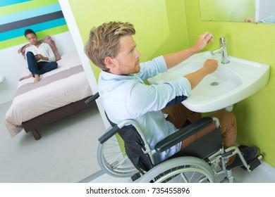 man on wheelchair washing hands in bathroom