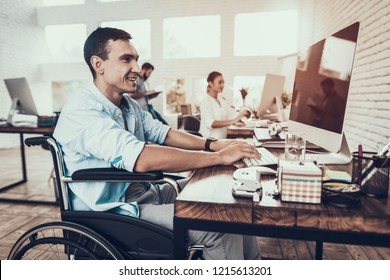 Man on Wheelchair Working on Computer in Office. Disabled Young Man. Wheelchair. Recovery and Healthcare Concepts. Teamwork in Office. Young Worker. Sitting Man. Man with Computer.
