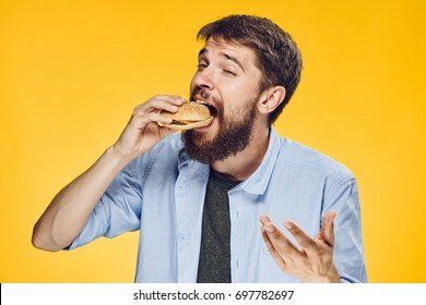Man on a yellow background eating a hamburger.