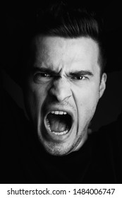 A man with an open mouth screams fear stress Studio
