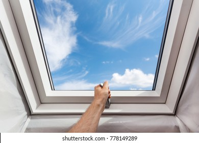 Man open new skylight (mansard window) in an attic room against blue sky