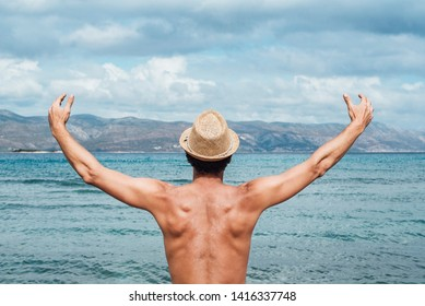 Man with opened arms say hey to the big blue sea