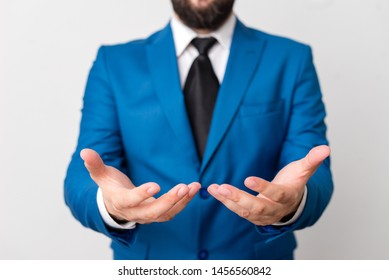 Man with opened hands in fron of the table. Mobile phone and notes on the table. Business concept with man in the suite.