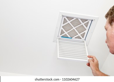 Man Opened a Vent to a Dirty Filter. Mature adult opening a small square HVAC air intake vent revealing a dirty air filter in the ceiling. Man opened a a vent grill cover to dirty ceiling air filter