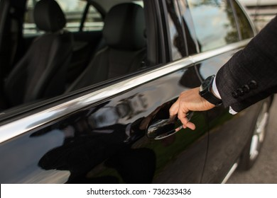 Man opening a black car limousines door