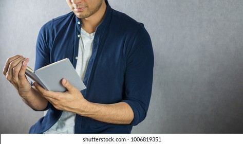 Man opening book, look happy on grey background