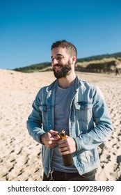 Man opening a bottle of beer on the beach on a sunny day