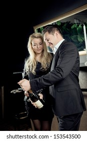 A Man is opening a bottle of wine.
