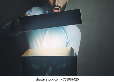 man is opening a box with something exciting inside it