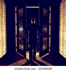 Man opening closing front double entryway doors with glass in foyer at night from behind looking curious afraid creepy welcoming leaving entering the unknown darkness possibility ready for the future
