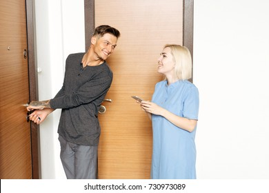 man is opening door with keys while woman is unblocking the alarm from her smartphone. Smart home concept