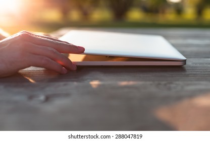 Man opening his laptop on a wooden table at sunset.