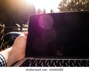 Man opening up his laptop, outdoors, with lens flares