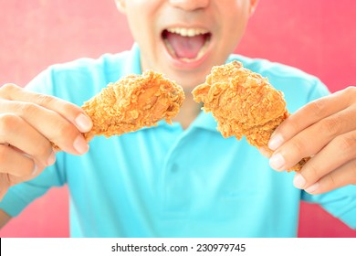 A man with opening mouth about to eat deep fried chicken legs or drumsticks