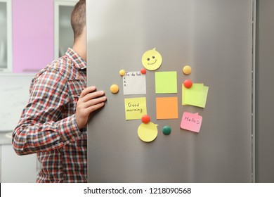 Man opening refrigerator door with paper sheets and magnets at home, closeup