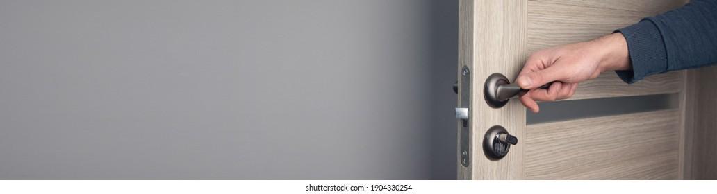 man opening wooden door in room