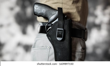 Man openly carrying a revolver in a holster on his belt. Open carry and second amendment concept.