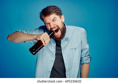 Man opens a bottle of beer with his teeth on a blue background
