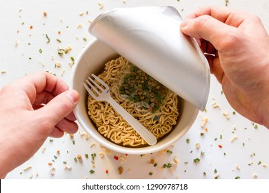 man opens the box with instant noodles