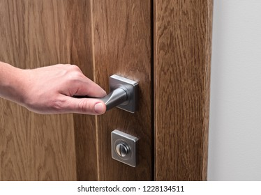 The man opens the door. Close - up of hand and door handle. Dark solid oak door.