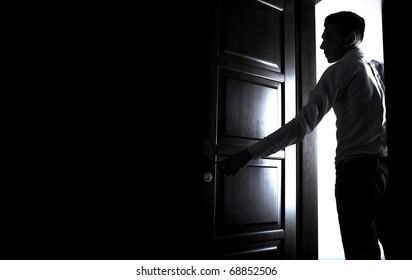 Man opens the door to dark room