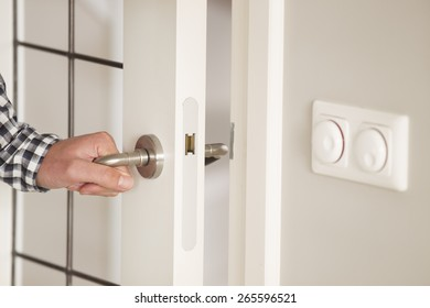 Man opens door of a house or a room