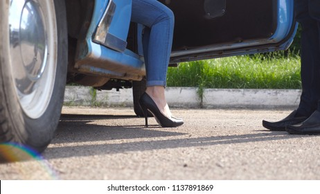 Man opens and holds door of retro car for young woman in high heels shoes. Chauffeur opening door of vintage automobile for female passenger. Legs of girl getting into old auto. Close up Slow motion.