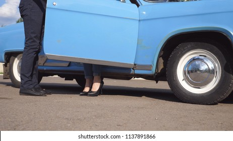 Man opens and holds door of vintage car for the beautiful woman in high heels shoes. Chauffeur opening door of old automobile for female passenger. Legs of girl getting out of retro auto. Close up.