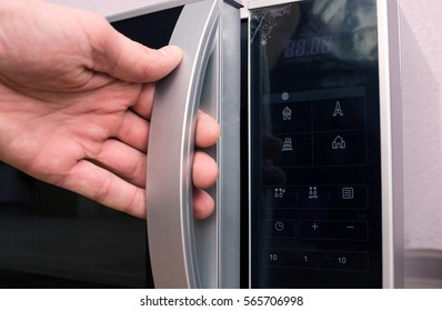 Man opens microwave in the kitchen
