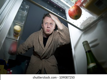 Man opens Refrigerator looking for a midnight snack