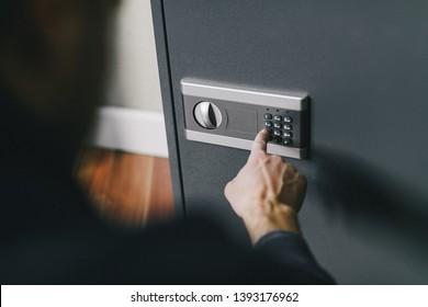 man opens safe, combination lock
