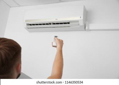 Man operating air conditioner with remote control indoors