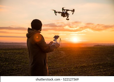 Man operating a drone with remote control. Dark silhouette against colorful sunset. Soft focus.