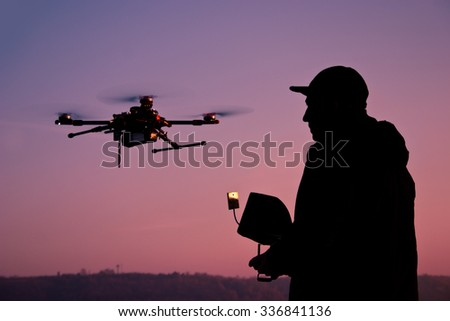 Man operating a drone with remote control. Dark silhouette against colorfull sunset. Soft focus. Toned image