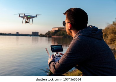 Man operating / flying with drone by the river at sunset , closeup and back view shot