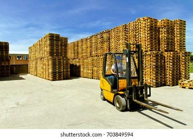 Man operating forklift inside of pallet warehouse